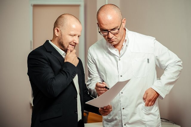 Two gentlemen looking at a paper.